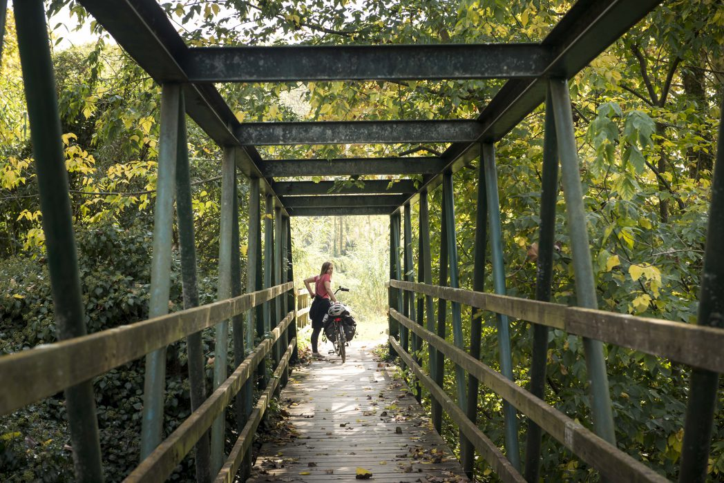 Girl with a bicycle waiting on a bridge