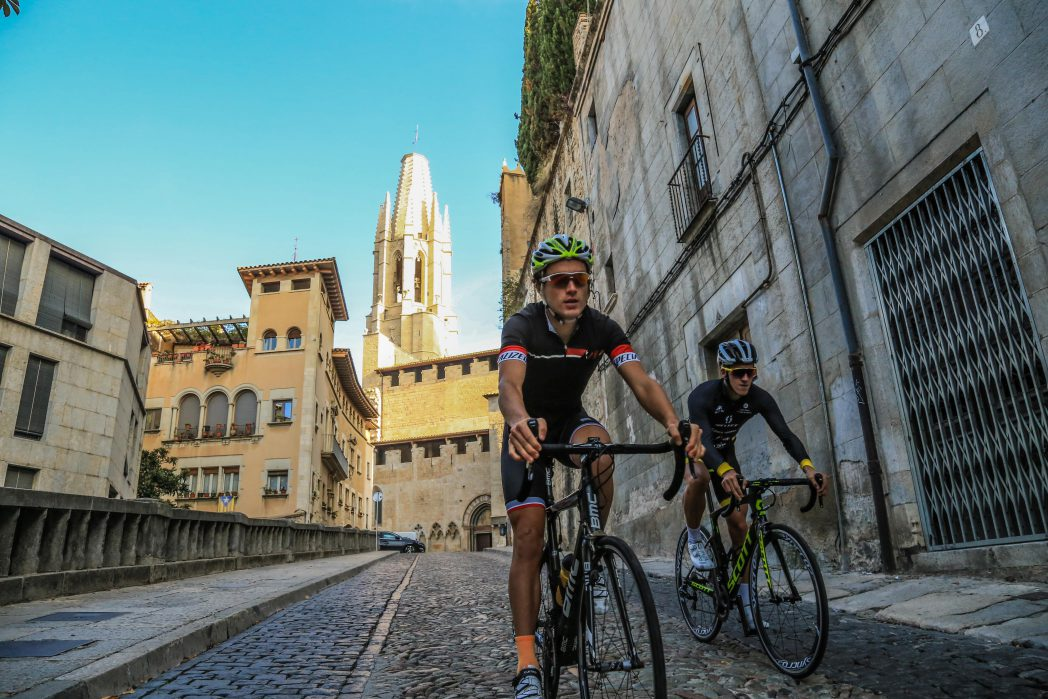 Two cyclists near Sant Feliu church in Girona
