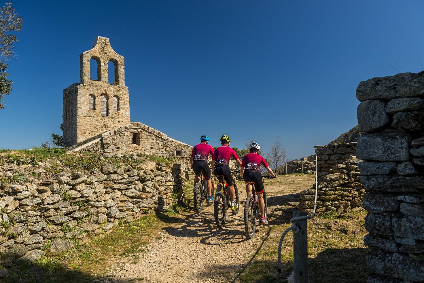 Tres ciclistes davant una ermita