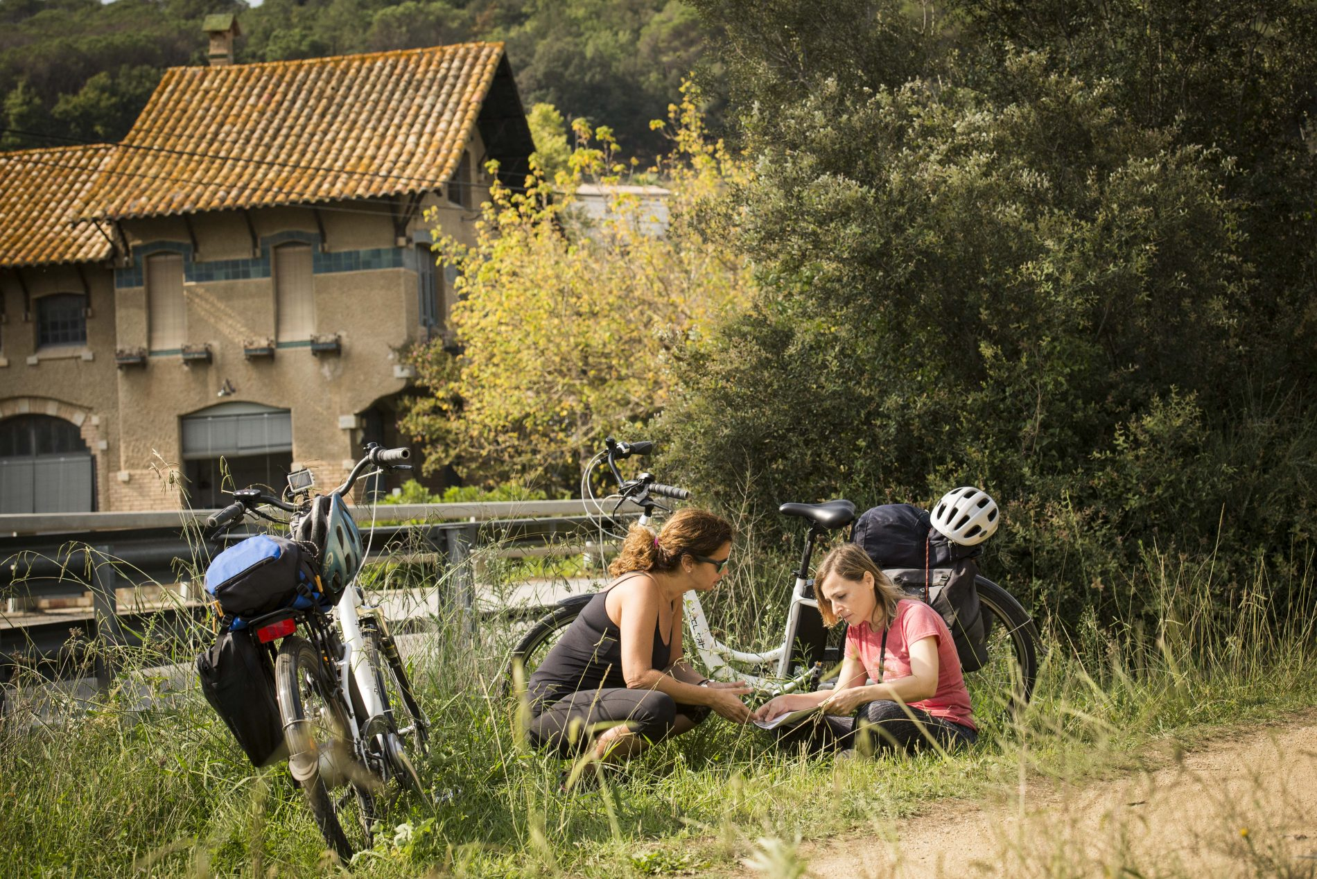 Dos ciclistas mirando un mapa, al lado de la central hidroléctrica de Bescanó
